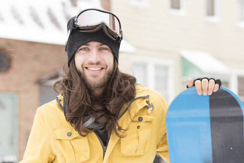 Portrait of young man holding snowboard on street - ISF10790