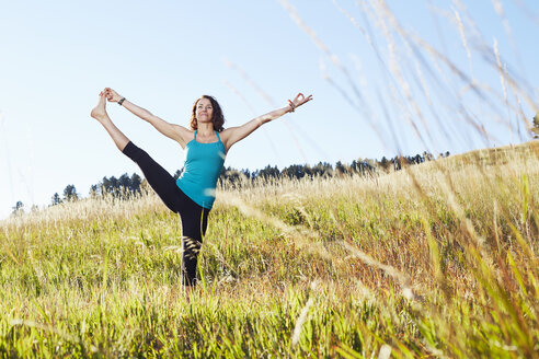 Mature woman practising yoga on field - ISF10814