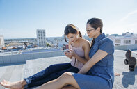 Businesswomen using smartphone on roof terrace, Los Angeles, California, USA - ISF11021