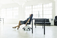 Businesswoman exhausted on chair by office window - ISF11024