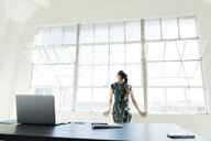 Businesswoman looking out of office window - ISF11027