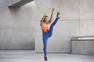 Front view of young woman wearing sports clothing arms raised, leg raised exercising - ISF11153