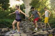 Joggers crossing stream under arch bridge, Arroyo Seco Park, Pasadena, California, USA - ISF11339