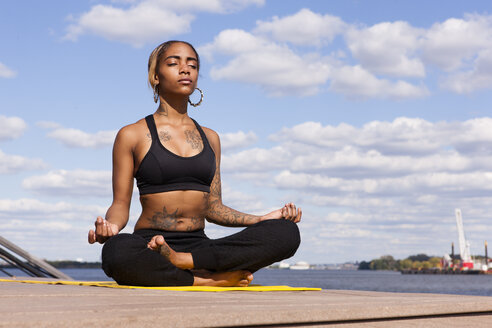 Young woman sitting cross legged by water in yoga position, eyes closed, Philadelphia, Pennsylvania, USA - ISF11354
