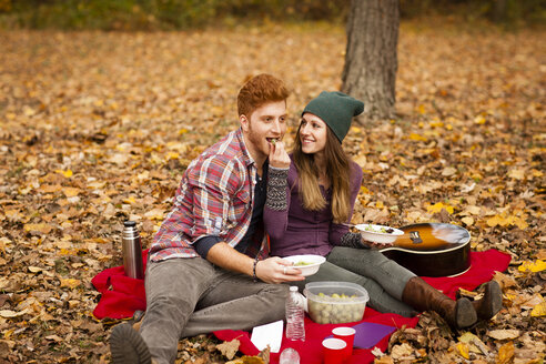 Young couple having picnic in autumn forest - ISF11372