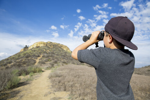 Boy looking through binoculars at landscape, Thousand Oaks, California USA - ISF11570