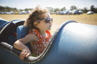 Girl sitting in barrel cart, wearing sunglasses looking away - ISF11603