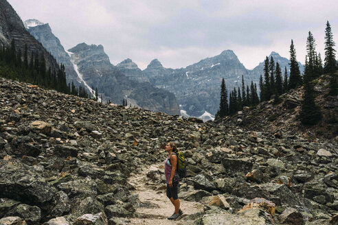 Side view of mid adult woman on rocky landscape beneath mountain range, Moraine lake, Banff National Park, Alberta Canada - ISF11651