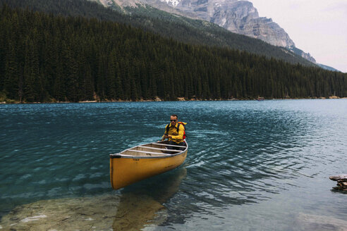 Mid adult man paddling canoe on Moraine lake, looking at camera, Banff National Park, Alberta Canada - ISF11690