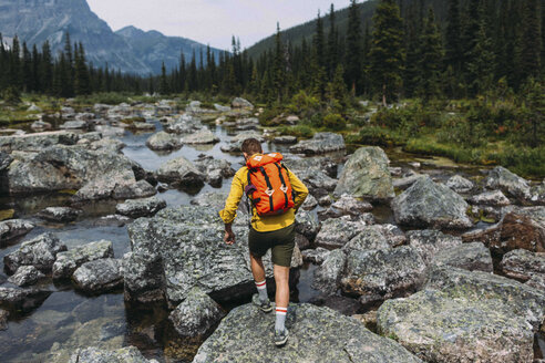 Rear view of mid adult man carrying backpack walking on rocky riverbed, Moraine lake, Banff National Park, Alberta Canada - ISF11696
