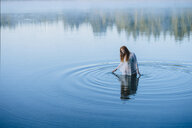 Young woman standing in middle of lake ripples looking down - ISF11906