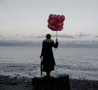 Woman holding bunch of red balloons standing large driftwood tree stump on beach - ISF11936