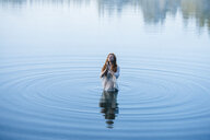 Young woman standing in lake ripples praying with eyes closed - ISF11942