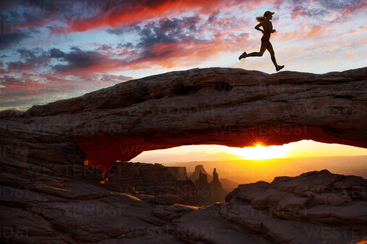 Young female runner running over rock formation at sunset, Moab, Utah, USA - ISF11951 - Pete Saloutos/Westend61