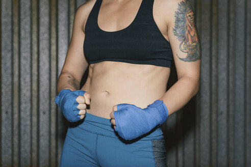 A cropped portrait of young woman exercising and boxing punching towards the camera with arm tattoo - ISF11999