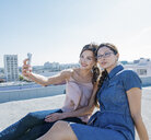 Businesswomen taking selfie with smartphone on roof terrace, Los Angeles, California, USA - ISF12020