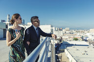 Businessman and businesswoman looking at view on roof terrace, Los Angeles, California, USA - ISF12023