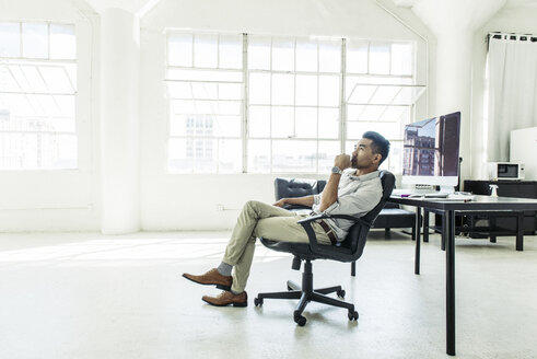 Businessman contemplating by office window - ISF12029