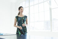 Businesswoman in patterned dress by office window - ISF12032