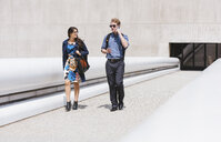 Businessman and woman walking and talking in city - ISF12059