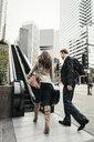 Businesswoman and man walking toward escalator, Los Angeles, USA - ISF12062