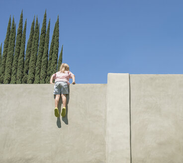 Young boy looking over tall wall, feet dangling, rear view - ISF12170