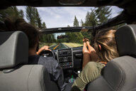 Rear view of young couple on the road in jeep - ISF12233