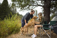Young couple petting dog at campsite, Lake Tahoe, Nevada, USA - ISF12239