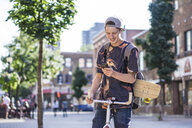 Young man using smartphone on bicycle, Le Plateau, Montreal, Quebec, Canada - ISF12308