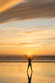 Rear view of mid adult nude womans silhouette standing on beach at sunset, legs apart, arms raised - ISF12356