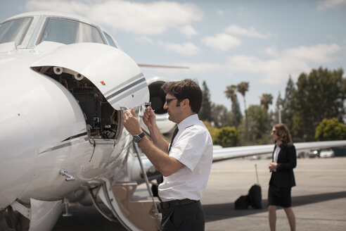 Male pilot checking private jet at airport - ISF12395