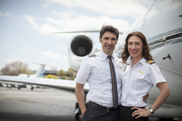 Portrait of male and female private jet pilots at airport - ISF12398