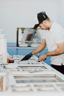 Young man preparing a roll of ice in an ice cream shop - OCAF00297