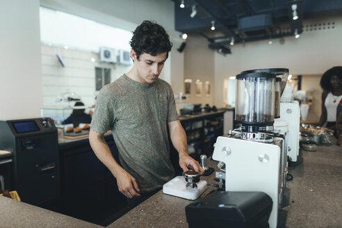 Barista preparing coffee in a coffee bar - OCAF00312
