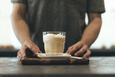 Waiter serving Latte Macchiato in a coffee bar - OCAF00324