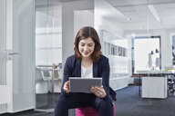 Young businesswoman using tablet in office - RORF01263