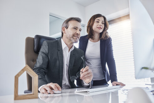 Businessman and businesswoman at desk in office with architectural model - RORF01269