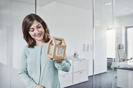 Smiling young businesswoman looking at architectural model in office - RORF01284
