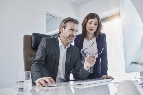 Businessman and businesswoman discussing at desk in office - RORF01287