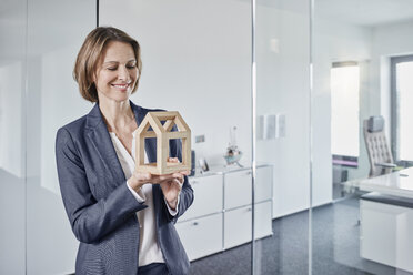 Smiling businesswoman looking at architectural model in office - RORF01290