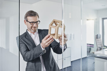 Smiling businessman looking at architectural model in office - RORF01296