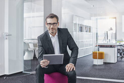 Portrait of confident businessman using tablet in office - RORF01302