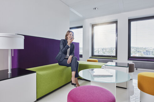 Businesswoman using smartphone in office lounge - RORF01323