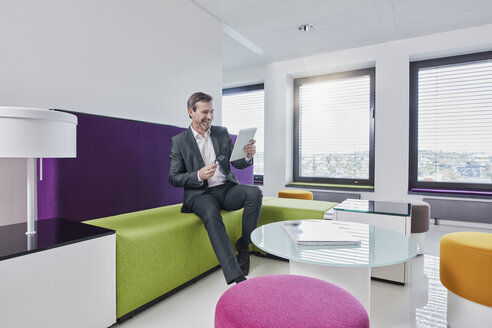 Happy businessman with tablet in office lounge - RORF01329