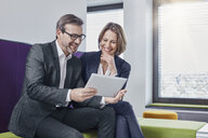 Smiling businessman and businesswoman using tablet in office lounge together - RORF01332