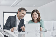 Businessman and businesswoman having a meeting in office with laptop - RORF01335