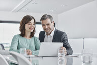 Businessman and businesswoman having a meeting in office with laptop - RORF01338