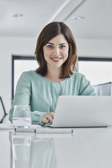 Portrait of smiling young businesswoman using laptop at desk in office - RORF01341
