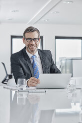 Portrait of smiling businessman with laptop at desk in office - RORF01344