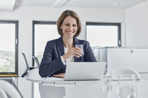 Portrait of smiling businesswoman using laptop at desk in office - RORF01347